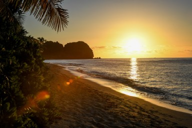 A fiery sun sets over the Pacific at Vomo Island in Fiji