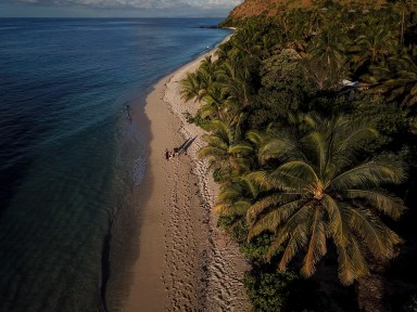 An aerial shot of the family strolling on the beach strip at Vomo Island Fiji