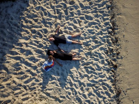 An aerial view of the family making snow angels in the sand