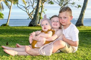 Portrait of siblings sitting on the lawn of the Shangri in Fiji