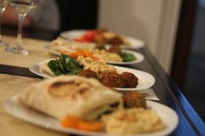 Pită de casă cu falafel, humus, sos tahinni și salată de roșii cu spanac