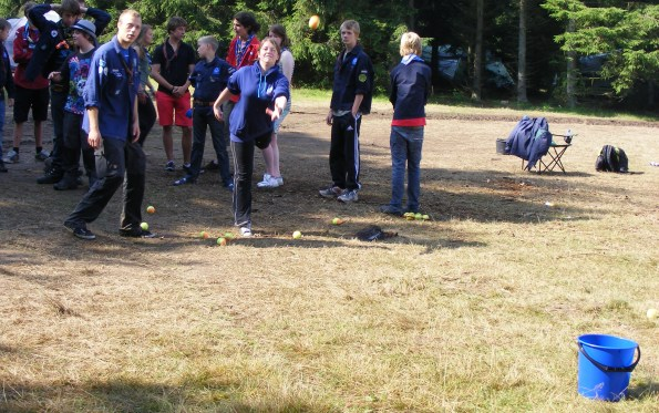 AT IT GIRL_Assistant Patrol Leader Natalie throws a ball in a bucket, during the mini-Olympics event.