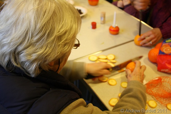 CUT ITS BOTTOM OFF_Ann Darracott assists with the flattening of the bottoms of the oranges.