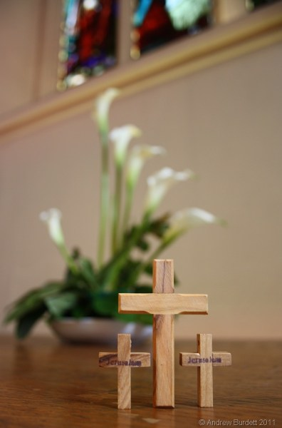 Easter lilies and three crosses sit on the bare altar at St Luke's Church, Maidenhead.