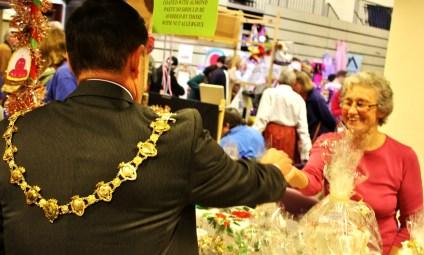 Mayor Andrew Jenner handing over money to the St Luke's stall.