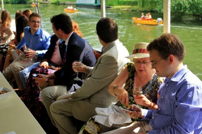Guests enjoying the pleasant weather from the shelter of the party boat's canopy.