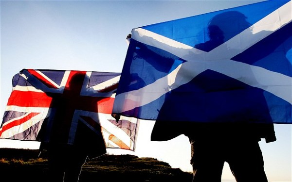 Sunlight forms silhouettes of campaigners on the flags of the United Kingdom and Scotland.