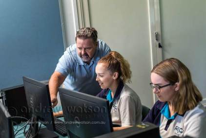Teacher assisting students in IT class