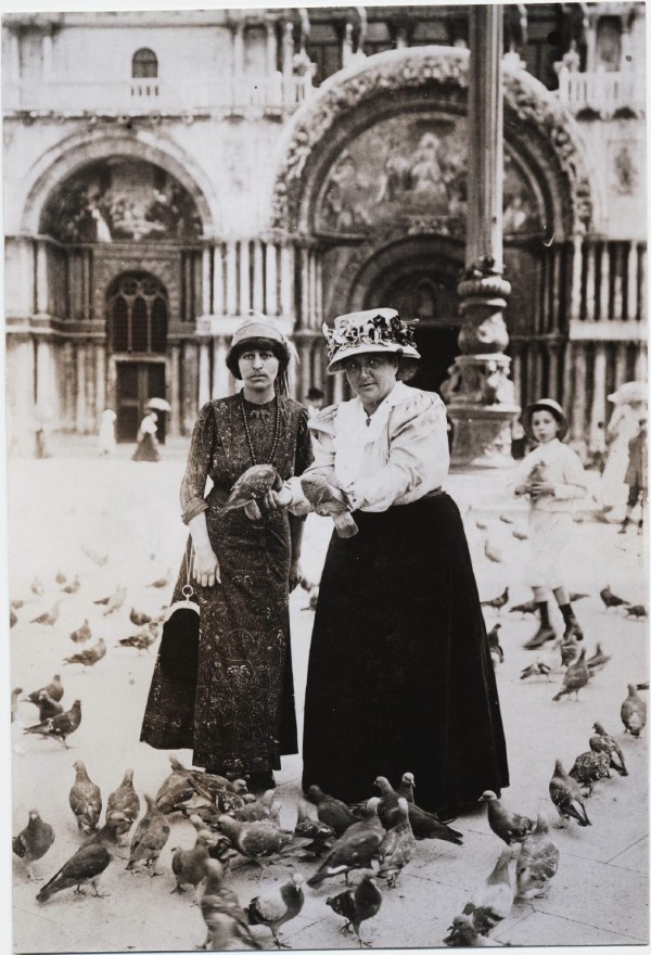 Alice B. Toklas and Gertrude Stein in a plaza, with pigeons, ca. 1908.