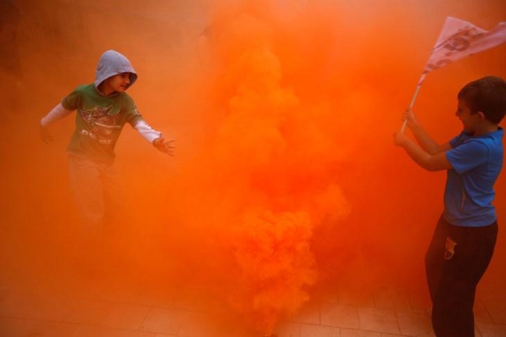 Αγόρια παίζουν με ένα δοχείο καπνού κατά τη διάρκεια διαδήλωσης από τους πυροσβέστες, την ασφάλεια και το στρατιωτικό προσωπικό ενάντια στις περικοπές των μισθών που τους επιβλήθηκαν  από την ισπανική κυβέρνηση, στην πρωτεύουσα της Ανδαλουσίας της Σεβίλλης