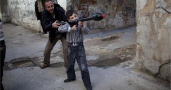 Ανδρας μαθαίνει τα «μυστικά» του πολέμου και των όπλων στον 11χρονο Μπιλάλ στη βόρεια Συρία.Από τη σειρά φωτογραφιών του ΑΡ που κέρδισαν τον διαγωνισμό Πούλιτζερ. (AP Photo/Rodrigo Abd, File)