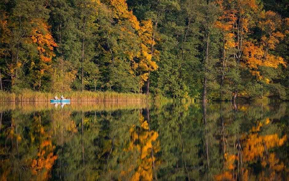Δύο ψαράδες με τη βάρκα τους, και το φθινοπωρινό σκηνικό της λίμνης Treplin της Γερμανίας, αντανακλώνται στα νερά της.