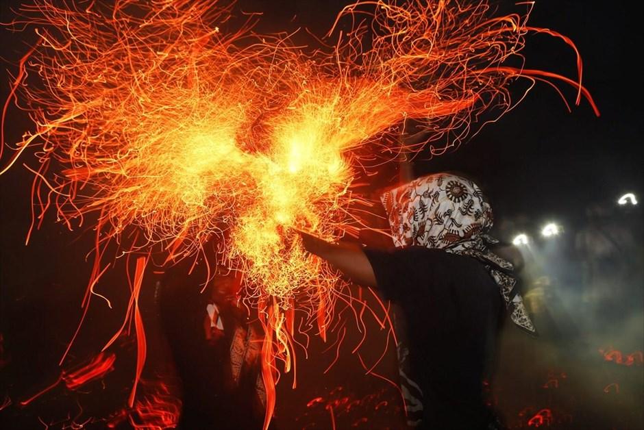 Δύο άνδρες μάχονται, κρατώντας με γυμνά χέρια, φλεγόμενους φλοιούς κοκοφοίνικα, στο πλαίσιο της «μάχης της φωτιάς» (Mesabatan Api), σε ναό του Τουμπάν στο Μπαλί της Ινδονησίας. Οι κάτοικοι του Μπαλί συμμετέχουν στο ιερό αυτό ινδουιστικό τελετουργικό, πιστεύοντας ότι η φωτιά μπορεί να τους απαλλάξει από αρνητικές δυνάμεις.