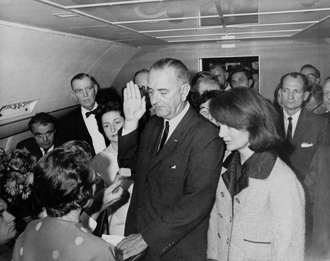 Η Jacqueline Kennedy φοράει το ροζ Chanel σακάκι, το οποίο είναι ακόμα λεκιασμένο με το αίμα του συζύγου της, την ίδια στιγμή που ο Lyndon Johnson ορκίζεται στο Air Force One.