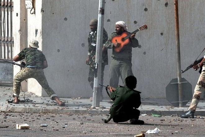ίβυος παίζει κιθάρα την ώρα που συναγωνιστές του πολεμούν. Η φωτογραφία τραβήχτηκε στις 10 Οκτωβρίου του 2011, στην Σύρτη της Λιβύης κατά την διάρκεια εχθροπραξιών. Η φωτογραφία είναι του Άρη Μεσσήνη. Ο φωτορεπόρτερ κέρδισε το πρώτο βραβείο του διαγωνισμού Bayeux- Calvados for War Correspondents (για πολεμικούς ανταποκριτές)