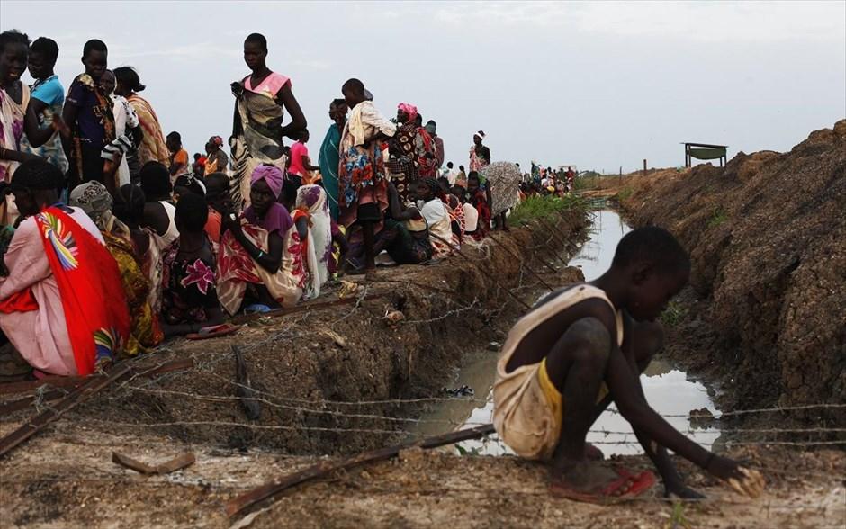 Εκτοπισμένες γυναίκες με τα παιδιά τους περιμένουν να ξεκινήσει η διανομή φαγητού σε ένα καταυλισμό εκτοπισμένων στην βάση του ΟΗΕ στο Μπεντιού, στο Νότιο Σουδάν. Ξεπέρασε τα 50.000.000, για πρώτη φορά από τον Β' Παγκόσμιο Πόλεμο, ο αριθμός των ανθρώπων που εγκαταλείπουν τις εστίες τους σε όλο τον κόσμο, εξαιτίας συγκρούσεων και κρίσεων.