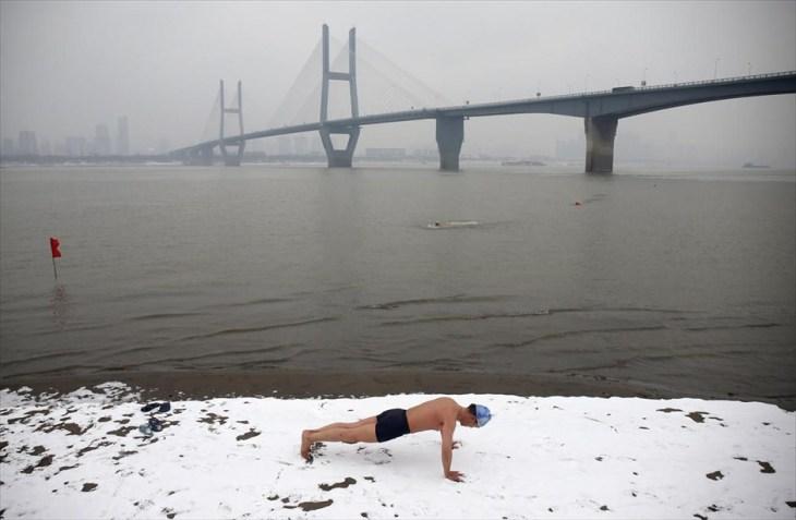 Χειμερινός κολυμβητής κάνει γυμναστική στη χιονισμένη όχθη του ποταμού Γιανγκτσέ, στο Γουχάν της Κίνας.