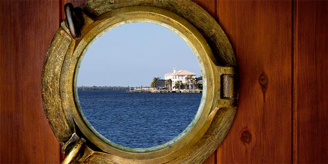 Close-up of a closed boat porthole with wihite background