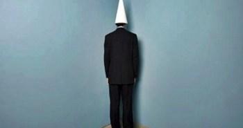 Businessman_wearing_dunce_cap_standing_in_corner
