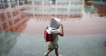 A school girl wearing a padded hood to protect her from falling debris, walks in school field during an earthquake simulation exercise at an elementary school in Tokyo