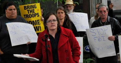 Anti-war activist Meredith Aby, center, whose home was raided by FBI agents in Minneapolis, is surrounded by supporters as she addresses the media, Friday, Sept. 24, 2010. The FBI said raids were made in Minneapolis and Chicago as part of a terrorism investigation. (AP Photo/Jim Mone)
