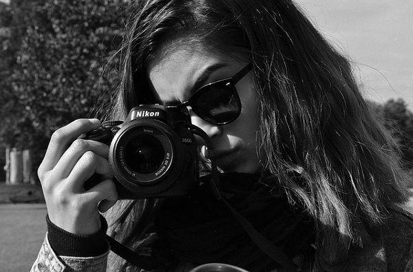 一眼レフカメラを向けるサングラスの女性