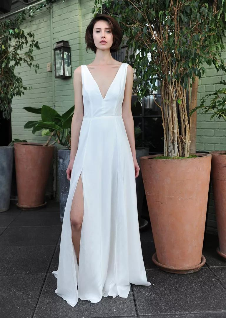 sarah seven wedding dresses bridal fashion week fall flowy wedding dresses Sarah Seven white sleeveless wedding dress with deep v neckline and high leg slit Fall