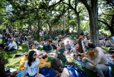 Eeyore's Birthday celebration is in its 52rd year at Pease Park in Austin, Texas.  People sit on a hillside in the shade. LAURA SKELDING / AMERICAN-STATESMAN