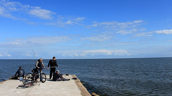 Four fishermen at the end of a dock by the Baltic Sea with blue sky in Lithuaia.