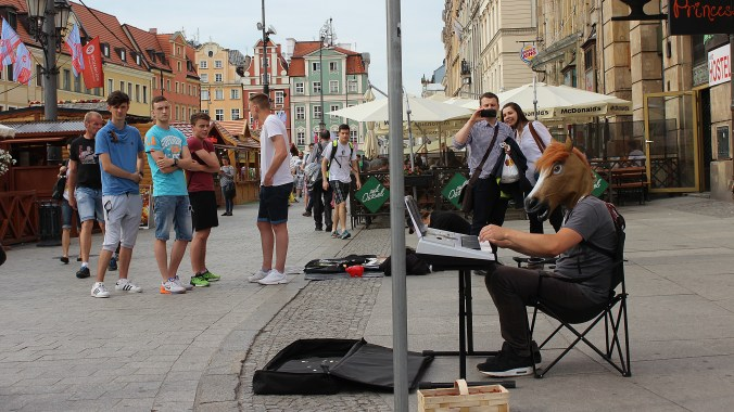 A street musician playing a keyboard with a horse mask in Wrocław, Poland.