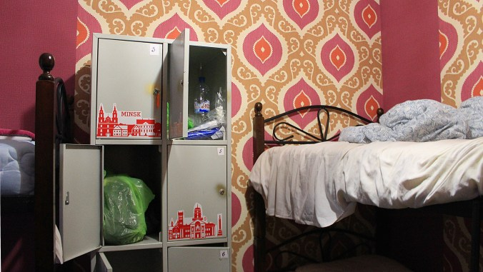 Backpacker hostel lockers in Belarus, Minsk with red and yellow tapestry in the background.