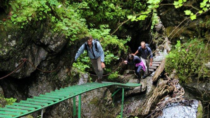 Slovakian hikers climbing a steel ladder in Slovenský Raj National Park, Slovakia.