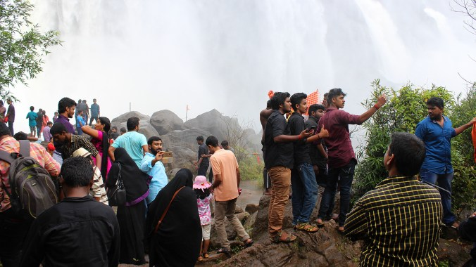 Indian tourists taking selfies below the Athirappilly Falls waterfall.