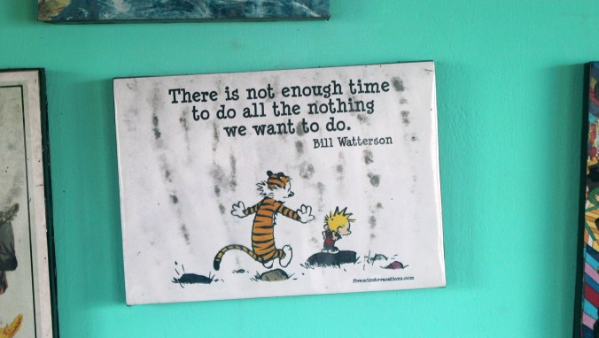 "A Calvin and Hobbes quote print saying ""There is not enough time to do all the nothing we want to do"" hanging on the wall of Zostel Gokarna, India."