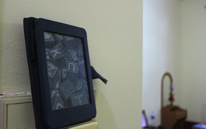 A 2nd generation Amazon Kindle Paperwhite model with the idle screensaver image.