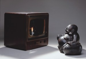 Нам Джун Пайк: Улыбающийся Будда (Buddha Looking at Old Candle TV), 1992 Металлический монитор, бронза, свеча (Будда: 40 x 60 x 30 см; Монитор: 55 x 55 x 48 см). © Nam June Paik Estate