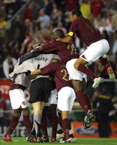 The players celebrate with Jens Lehmann after his save against Villarreal in 2006