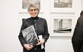 Erica Stoller holding her late father's book at his opening