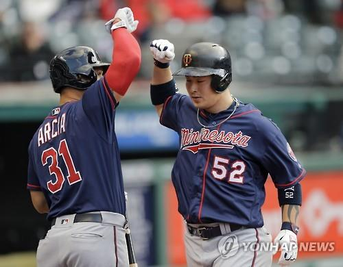Park Byung-ho of the Minnesota Twins (R) celebrates with Oswaldo Arcia after hitting a solo home run off Cleveland Indians' starter Josh Tomlin during their Major League Baseball game in Cleveland on May 13, 2016. (Yonhap)