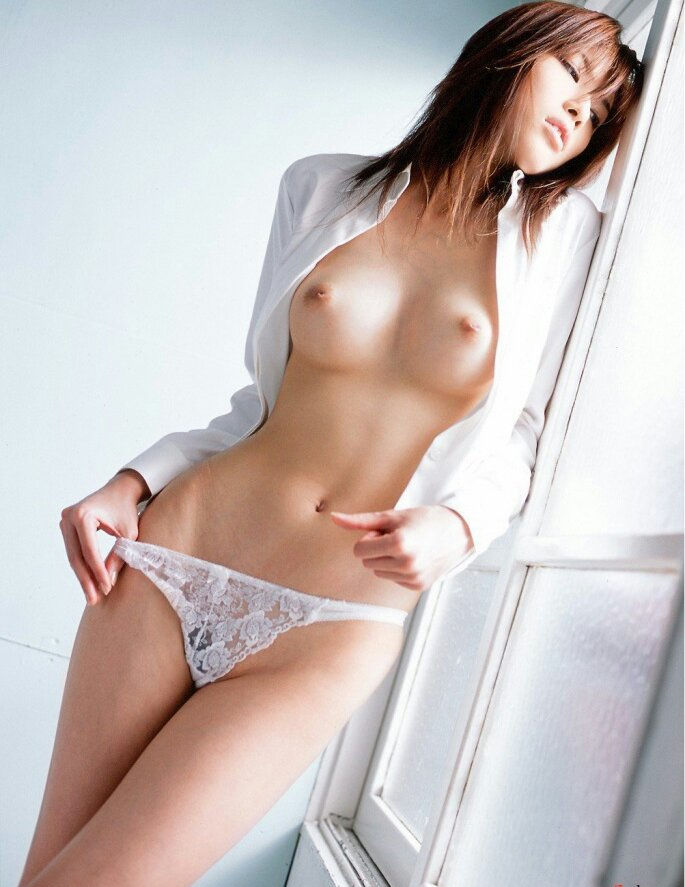Teen Asian brunette bitch is dreaming about sex, while standing next to the window.jpg