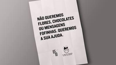 Folha de papel onde lê-se: Não queremos flores, chocolates ou mensagens fofinhas. Queremos a sua ajuda. 65|10 e Clube de Criação do Rio de Janeiro