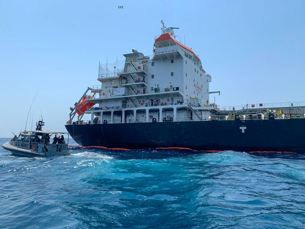 A U.S. Navy vessel guards the Japanese oil tanker Kokuka Courageous in the Gulf of Oman.