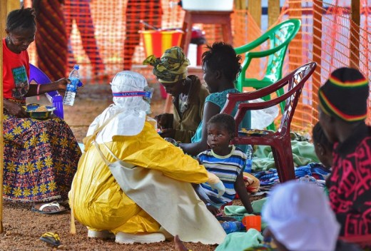 DAILY STRUGGLE. An Medecins Sans Frontieres (Doctors Without Borders) medical worker feeds an Ebola child victim at an MSF facility in Kailahun, Sierra Leone, on August 15, 2014. Carl de Souza/AFP