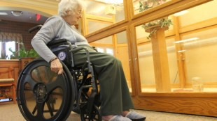 an elderly woman pushing a wheelchair that has Easy Push wheels installed.