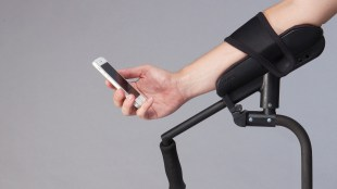 a person resting their arm on the arm rest of KMINa crutch and using their phone.