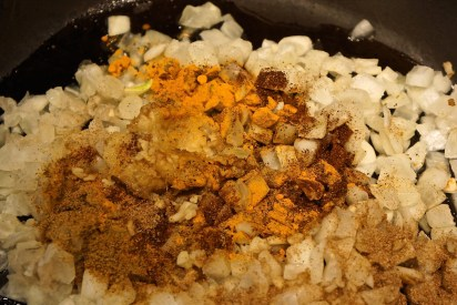 In a large skillet, heat oil over medium heat. Add onions, ginger, garlic, cumin, coriander, turmeric, chili powder and Garam Masala.