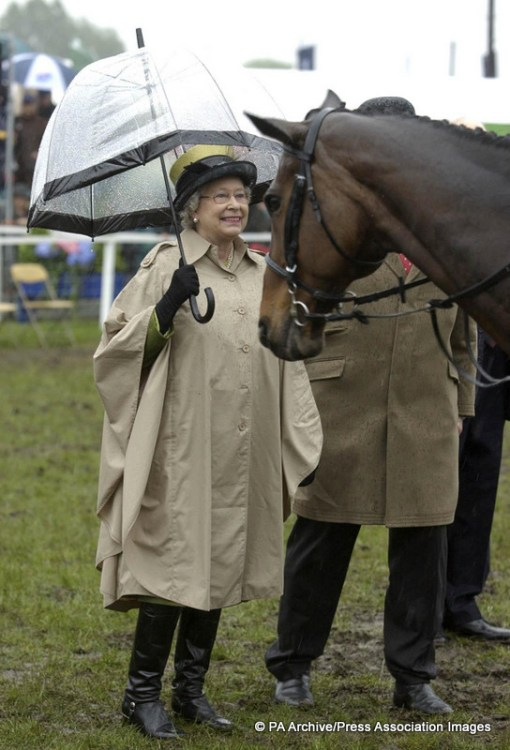 Queen Elizabeth happily braves the rain while presenting rosettes to the Services Team Jumping contestants at The Royal Windsor Horse Show. Image Source: PA Archives / Press Association Images.
