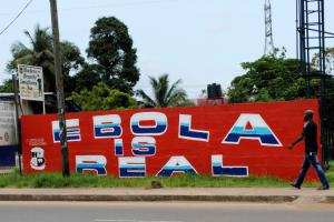 "A man walks by a mural reading ""Ebola is real"" in Monrovia"
