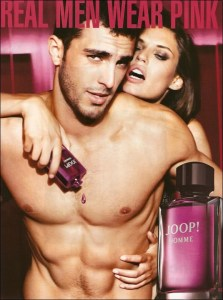 Joop advertisement. An attractive young man, with a bare torso and perfume dripping on his chest has a woman wrapped around his shoulders. Both are against a background of pink. The title reads: real men wear pink