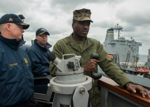 Cmdr. Charles Hampton, executive officer of the destroyer Donald Cook, gives instructions to Gunnery Sgt. Bathvill Valtin as he conns the ship during a replenishment at sea. Cook is leaving the Marine Corps for the Navy after being offered a commission there. (U.S. Navy photo by Mass Communication Specialist Seaman Adam Austin/Released)